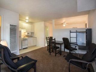 A Kitchenette on the left with a small dining table in the middle and office area on right