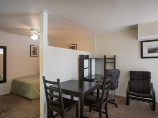 Apartment interior showing the bedroom on the left with a wall divider then the dining table and office area on the right